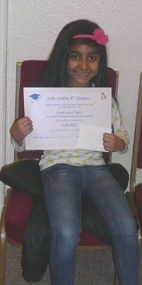 One of John Cashin's pupils showing her certificate  help your children achieve their goals